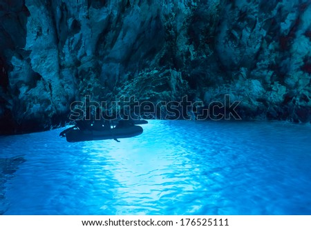 BISEVO, CROATIA - AUGUST 20, 2012: Tourists in inflatable boats inside the Blue cave, famous tourist attraction. - stock photo