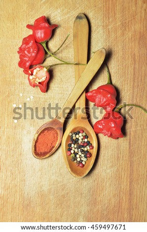 Bishop's crown chilli peppers and tomato spicy hot chili pepper sauce in a wooden spoon on the wooden background . Top view - stock photo