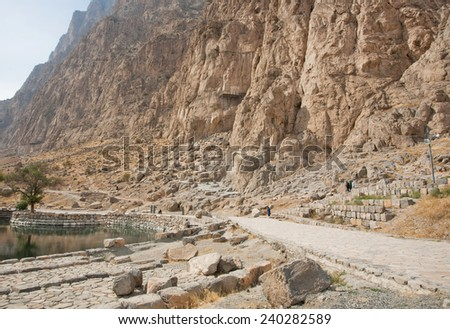 BISOTUN, IRAN - OCT 12: Iranian tourists walk past the mountain range in beautiful persian valley with rock reliefs on October 12 2014. Bisotun of Kermanshah Province is the UNESCO World Heritage site - stock photo