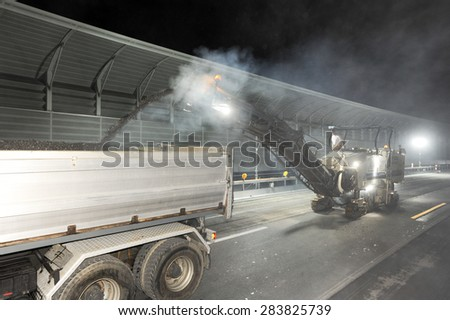 Bissone, Switzerland - 14 September 2007: Workers and vehicles during the road milling of the highway by night at Bissone on Switzerland - stock photo