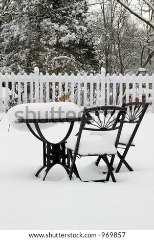 Bistro Set at Rest - garden furniture still after a snowstorm. - stock photo