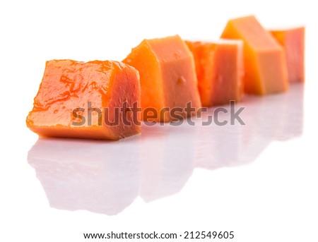 Bite sized papaya fruit over white background - stock photo