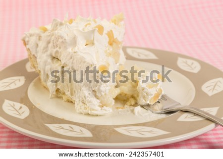 Bite taken from slice of Banana Cream Pie on dessert plate against pink gingham Country-Style  tablecloth.  Selective focus shallow depth of field - closeup. - stock photo