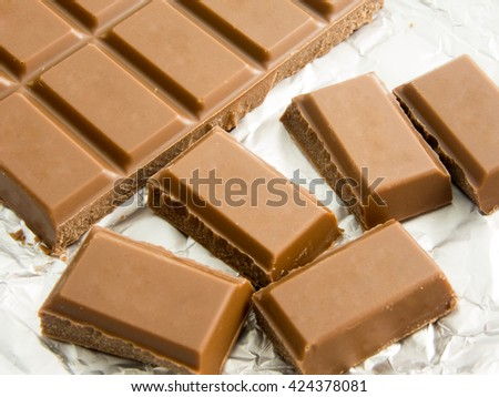 bites of delicious chocolate bar on foil packaging - stock photo