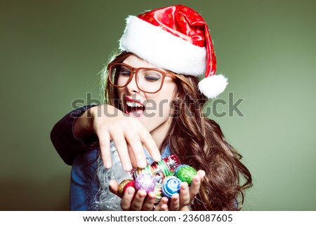 biting intruder's hand and saving Christmas tree decoration funny hipster girl in glasses wearing xmas santa hat over olive copy space background - stock photo