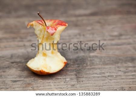 bitten apple on a wooden table - stock photo