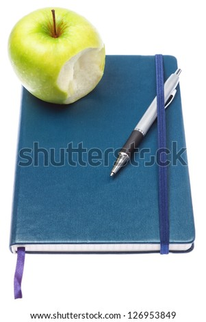 Bitten apple on notepad notebook and ballpoint pen. On a white background. - stock photo