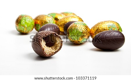 Bitten chocolate egg and other eggs in foil isolated on white background