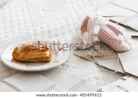 Bitten eclair with cream on plate and pink cute baby booties among paper letters on bed. - stock photo