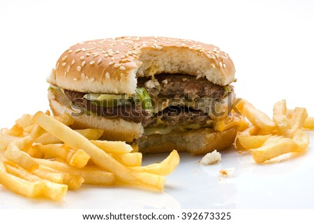 Bitten hamburger with french fries over white