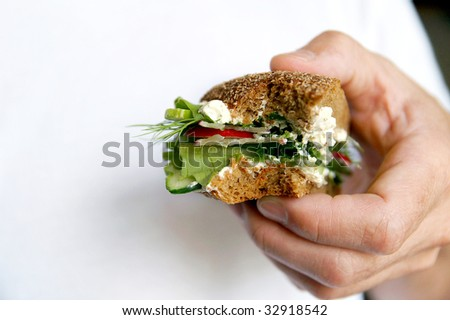 Bitten healthy rye bread sandwich with a plenty of fresh vegetables and herbs on a man's hand before a white T-shirt, blur background, close-up - stock photo