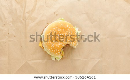 bitten off  burger on paper background. Top view - stock photo