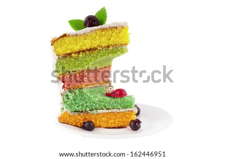Bitten rainbow cake decorated with a cherry on the top.  - stock photo