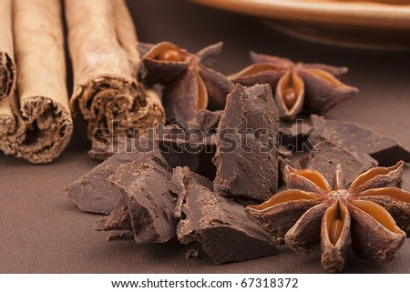 Bitter chocolate in pieces on a brown background with spices. - stock photo