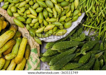 Bitter melon, cucumbers and longbeans at the indian market - stock photo