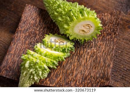 Bitter melon slice on wooden plate - stock photo