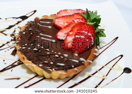 Bittersweet chocolate tartlet topped with sliced strawberry  - stock photo