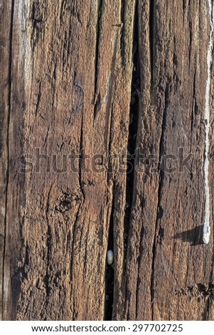 Bituminous rough surface texture of an old weathered, rotten, cracked Square Timber Bollard, made of obsolete, scrapped Railroad Cross Tie Timber. - stock photo