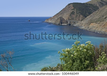 Bixby Bridge in Big Sur, California, on Highway 1 between the hillside and the Pacific Ocean with flowering plants in the foreground. - stock photo
