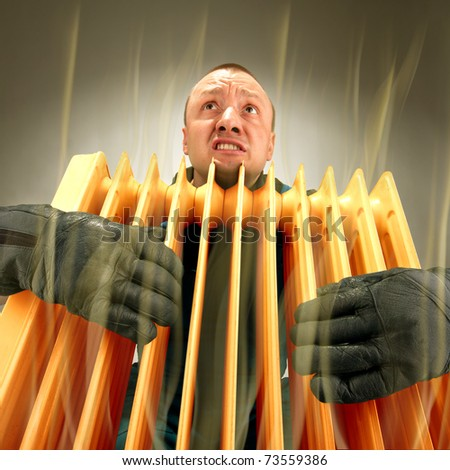 Bizarre freezing man holding hot oil radiator - stock photo