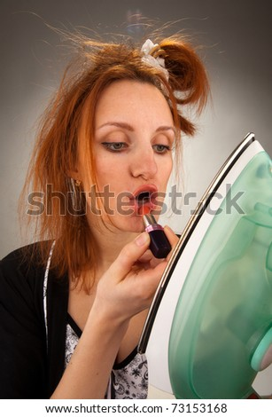 Bizarre housewife using lipstick looking to steam iron - stock photo