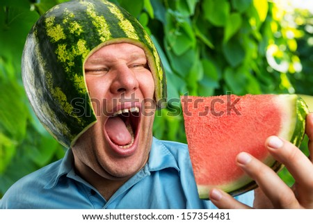 Bizarre man in a cap from a watermelon eating outdoors - stock photo