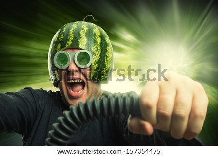 Bizarre man in a helmet from a watermelon riding fast - stock photo