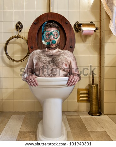 Bizarre man with goggles swimming in vintage toilet - stock photo