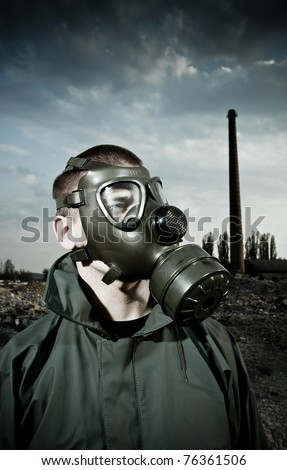 Bizarre portrait of man in gas mask on smoky industrial background with pipes after nuclear disaster - stock photo