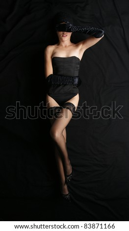Bizarre shoot of sexy lady in lingerie over black silk background - stock photo