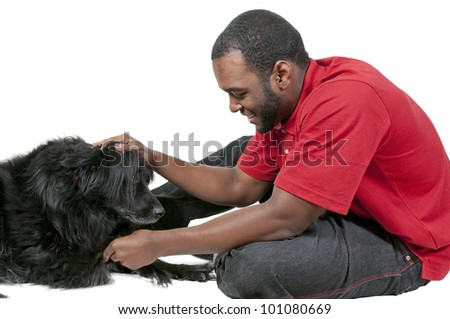 Black African American man playing with a dog - stock photo