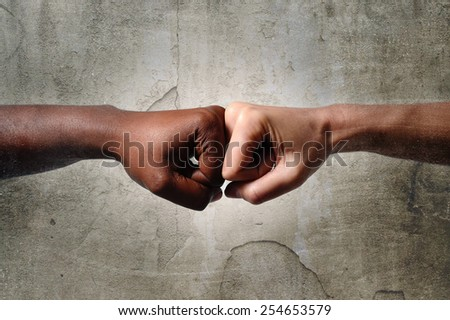 black African American race female hand touching knuckles with white Caucasian woman in agreement partnership and cooperation multiracial diversity immigration concept isolated on dirty background - stock photo