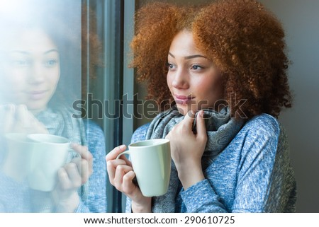Black African American teenage girl drinking a hot beverage and looking through a window - stock photo