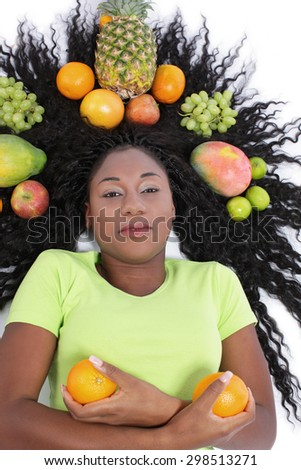Black african woman with lots of fresh fruits isolated on white