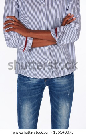 black african young adult businesswoman casually dressed in a blue pinstripe office shirt standing with crossed arms - body language