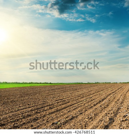 black agriculture field in spring and sunset in clouds - stock photo