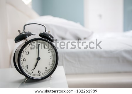 black alarm clock and bed - stock photo