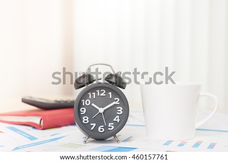 Black alarm clock and coffee place on wood table