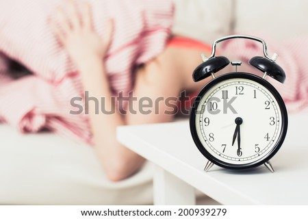 black alarm clock and woman - stock photo