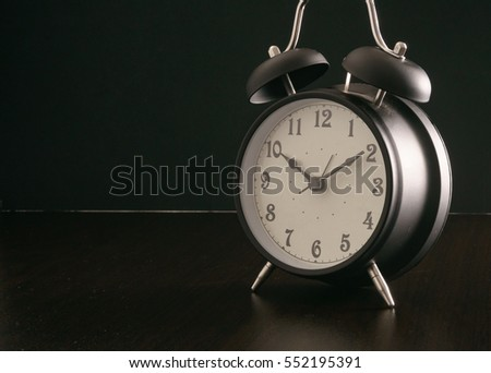 Black alarm clock on black desk