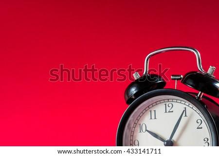 Black alarm clock on red background. clock concept. Alarm clock at ten o'clock five minute. - stock photo