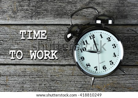 Black alarm clock on the rusty wooden table with word TIME to WORK - stock photo