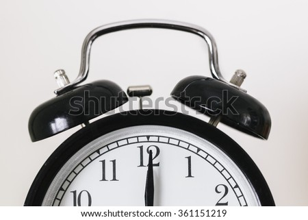 black alarm clock showing 12pm or 12am - stock photo
