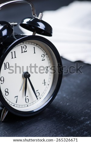 Black alarm clock with newspaper on a wooden table - stock photo