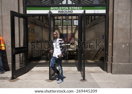 Black American waring headphones exits Boylston Street Outbound Subway Train with American Flag displayed, Boston MA - stock photo
