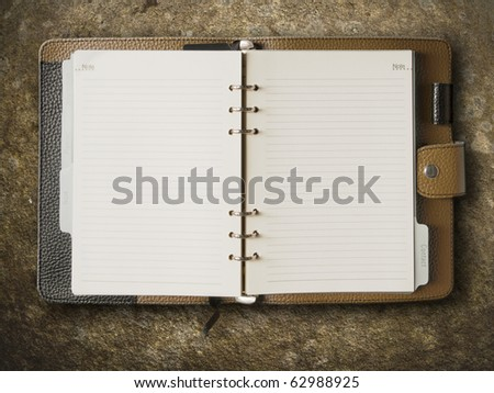 Black and brown leather cover of binder notebook on stone - stock photo