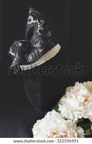 Black and cream lace fashion fascinator hat on hat block - stock photo