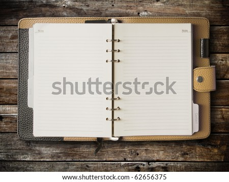 Black and cream leather cover of binder notebook on wood - stock photo