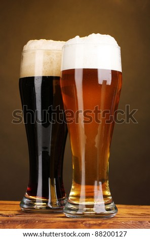 black and golden beer in glasses on wooden table on brown background - stock photo