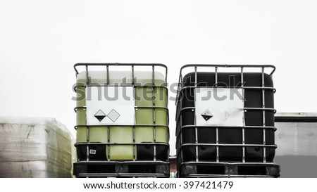 Black and green chemical container in a storage area - stock photo